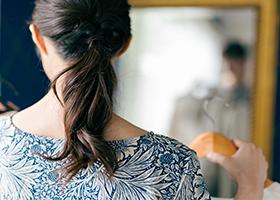 髪を括った女性の後ろ姿の写真